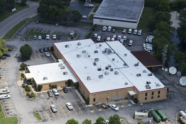 aerial view of white flat commercial building with parking lot filled with cars surrounding
