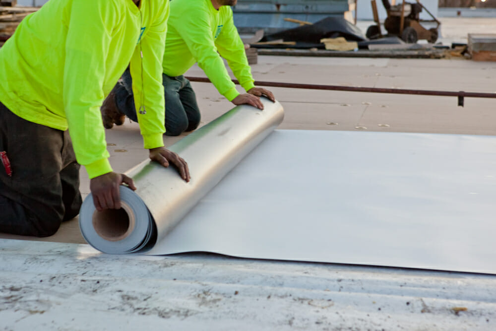two maxwell roofings on their knees unrolling a large metal sheet on a commercial roofing project