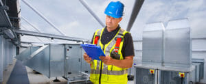 contractor on roof analyzing clipboard with information on it