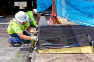 two Maxwell workers in process of working on roof installation