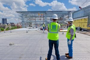 two maxwell engineers analyzing construction site on a sunny day with white clouds on a rooftop