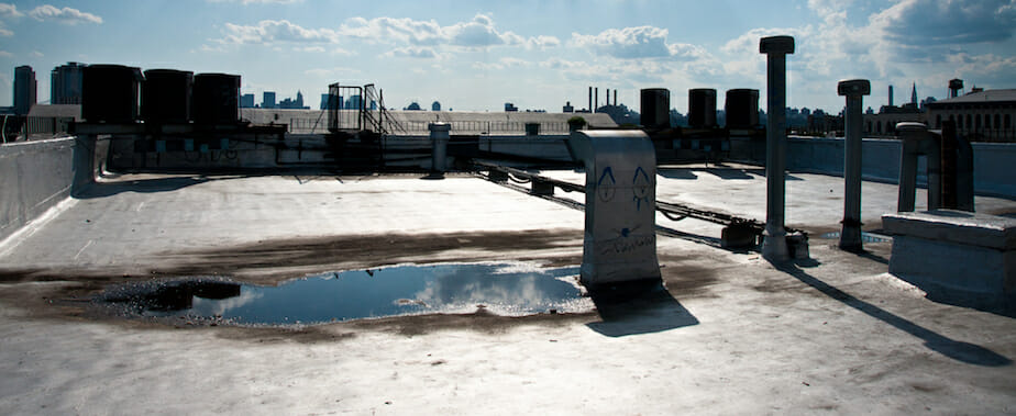 flat commercial roof with rain puddles collected from a previous storm