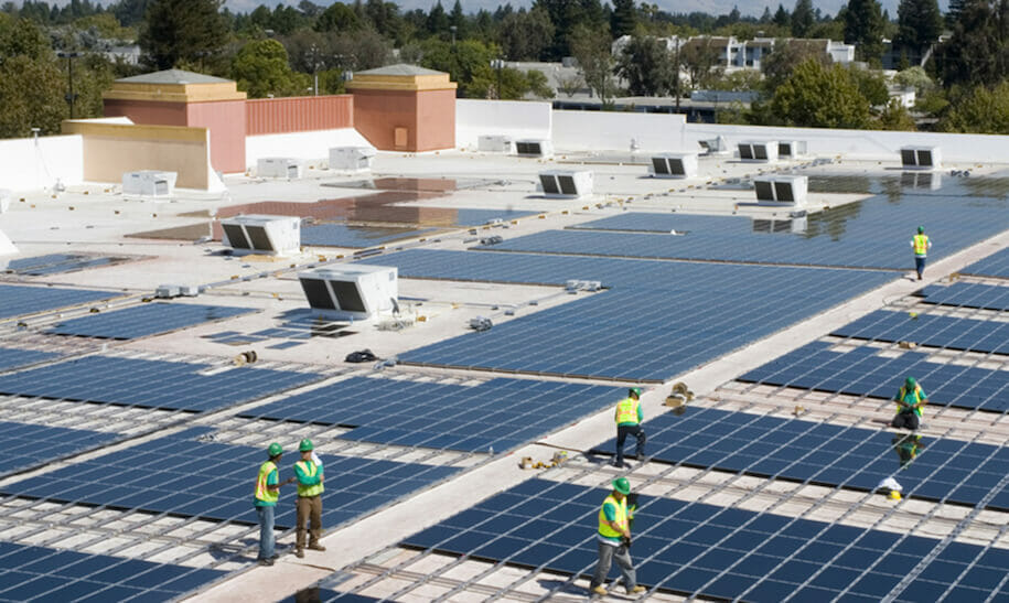 workers installing solar panels on a commercial roof