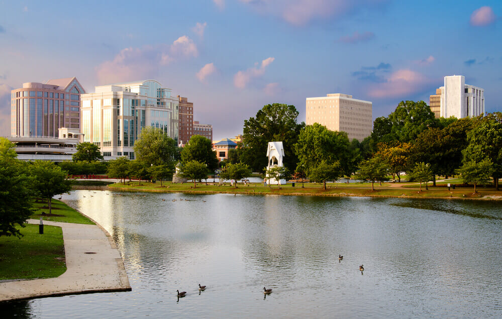 Huntsville, alabama river with skyline of the city in the background. ducks floating on the water.