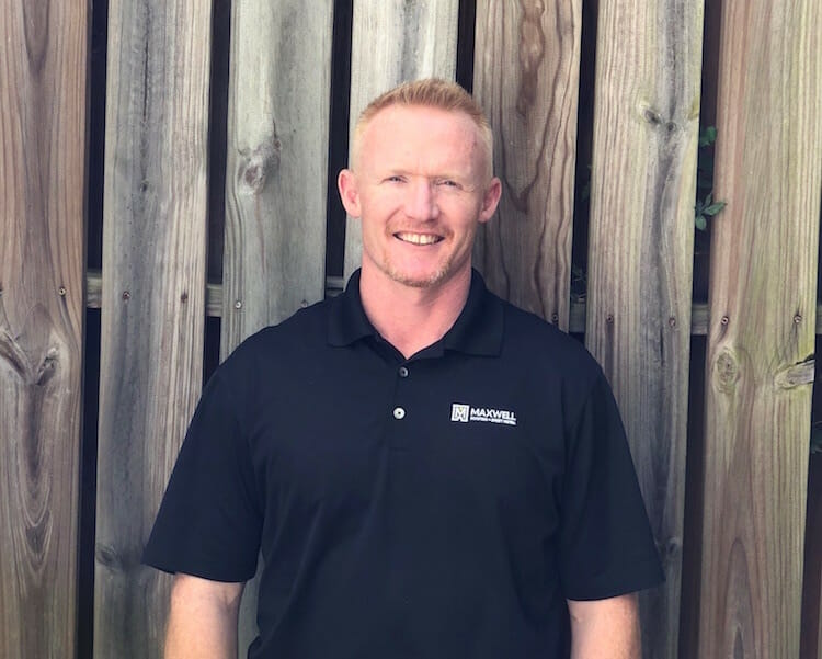 Brian Mecomber of Maxwell Roofing posing in front of tan wood backdrop for employee headshot