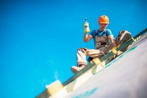 Worker on New Building Roof hammering
