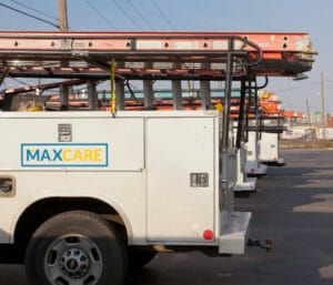 Maxwell roofing service trucks parked in a row in a parking lot with logo on the side