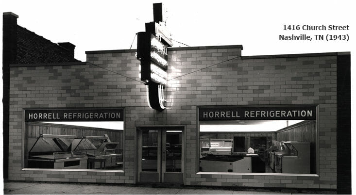 Horrell Company black and white store front with retro sign lit up