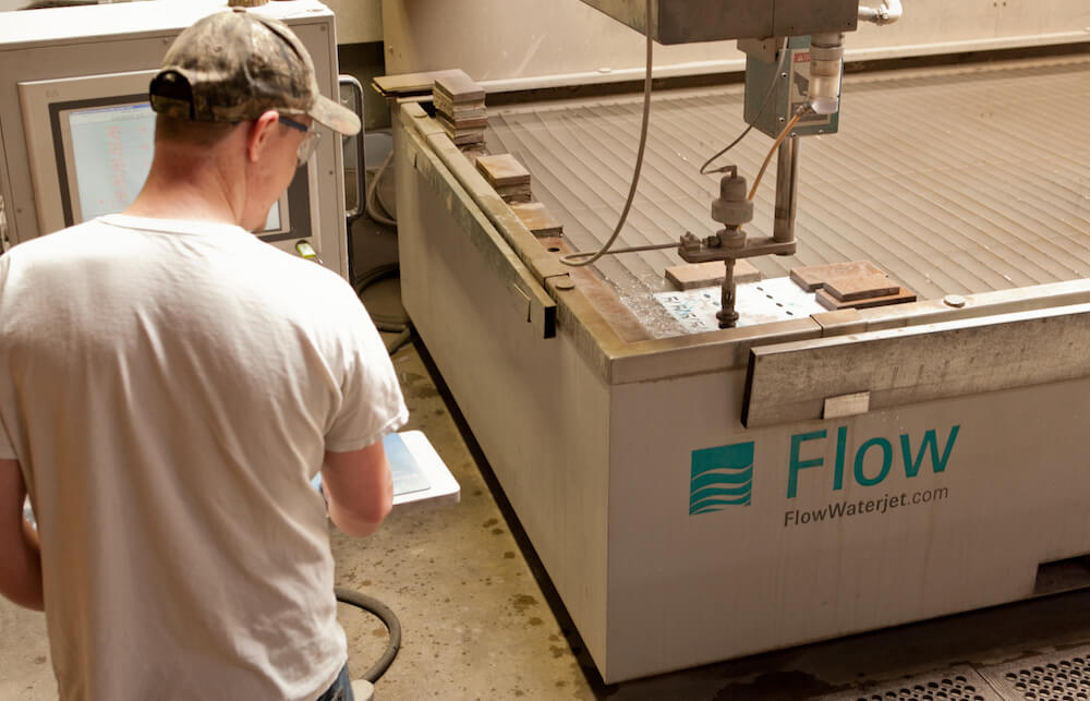 worker preforming in-house fabricating with a Flow waterjet