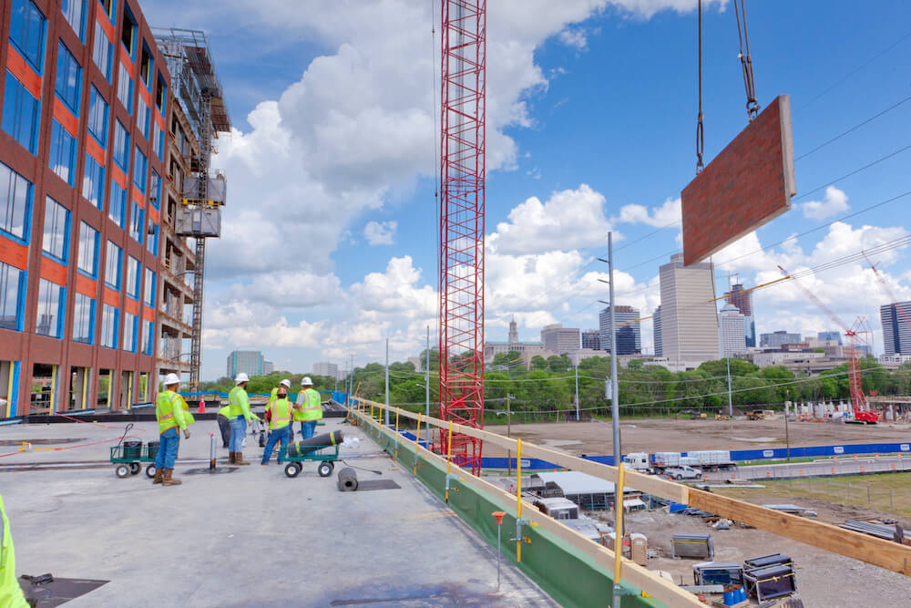 workers at construction site with a red crane lifting roof materials