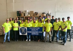 Maxwell roofing team members holding navy banner at the Fall 2018 Professional Skills Workshop
