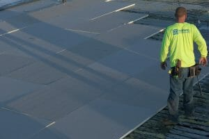 Maxwell worker with neon yellow shirt walking across unfinished roofing project as sun sets behind him