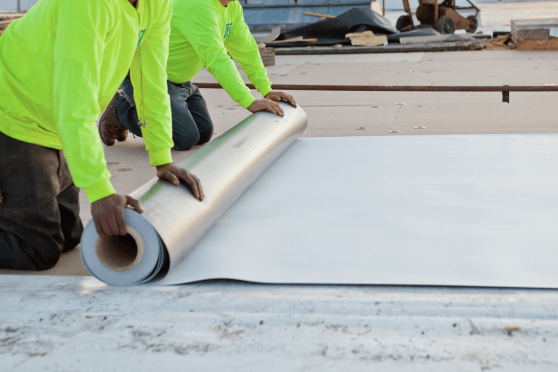 two maxwell roofers unrolling a large metal sheet on a commercial roofing project