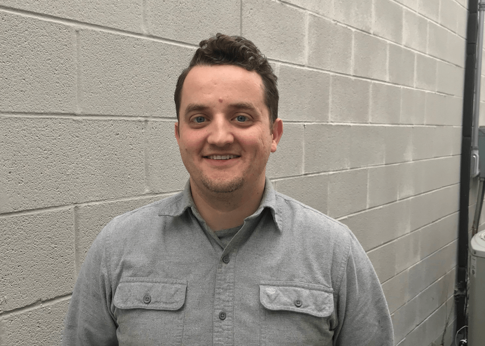 Job Carpenter of Maxwell Roofing standing against grey wall for employee spotlight photo