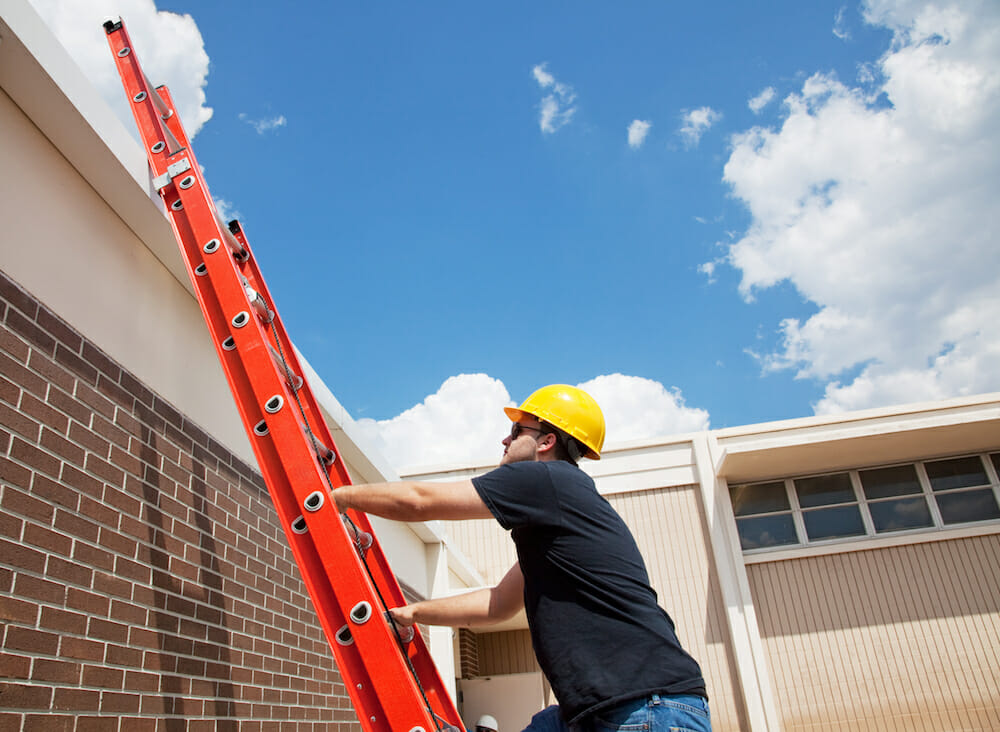 Worker climbing up a red ladder to the roof commercial building