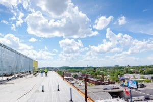 two roofers walking away on a commercial roof looking over The Factory in Franklin, Tennessee