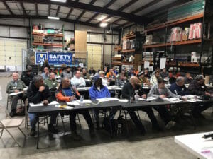 people sitting in a large factory setting sitting at tables in attendance of a CERTA event, CERTA Train-the-Trainer Certification
