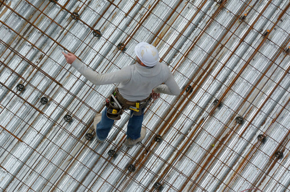 Aerial view of unrecognized roofer construction worker in a construction site. Building development concept with copy space