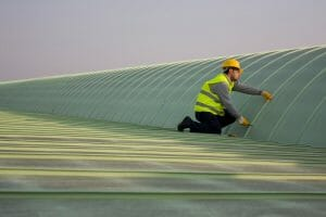 worker in neon yellow safety vest and yellow construction helmet working on metal commercial roof