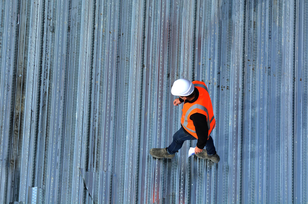 aerial view of worker in an orange safety vest and white helmet walking across metal commercial roof