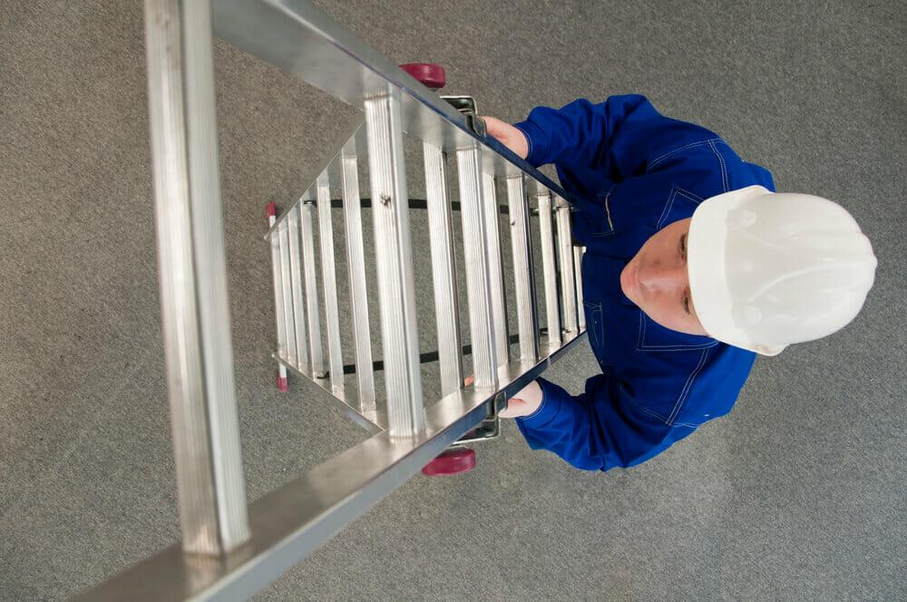 man in blue shirt with a white helmet climbing up a ladder