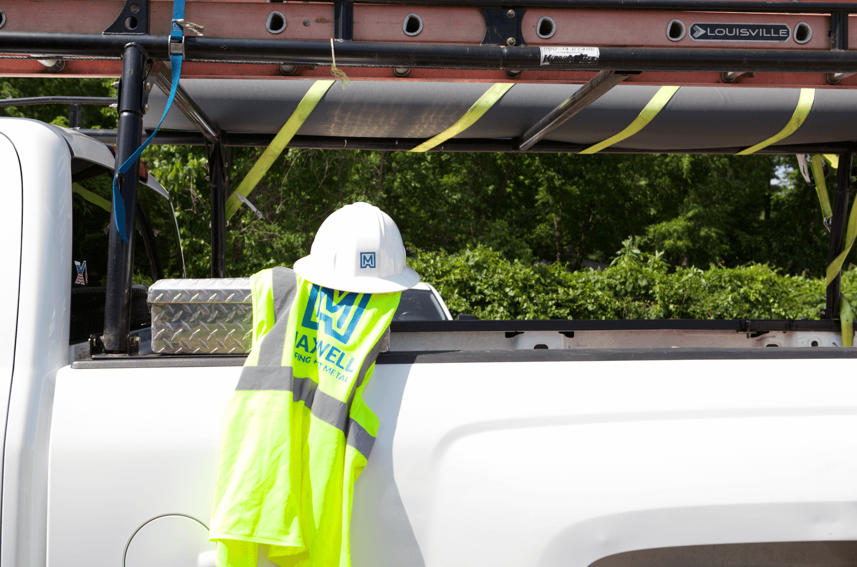 maxwell roofing safety vest and helmet draped over white service truck