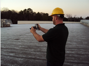 maxwell roofer taking infrared moisture survey on top of roof