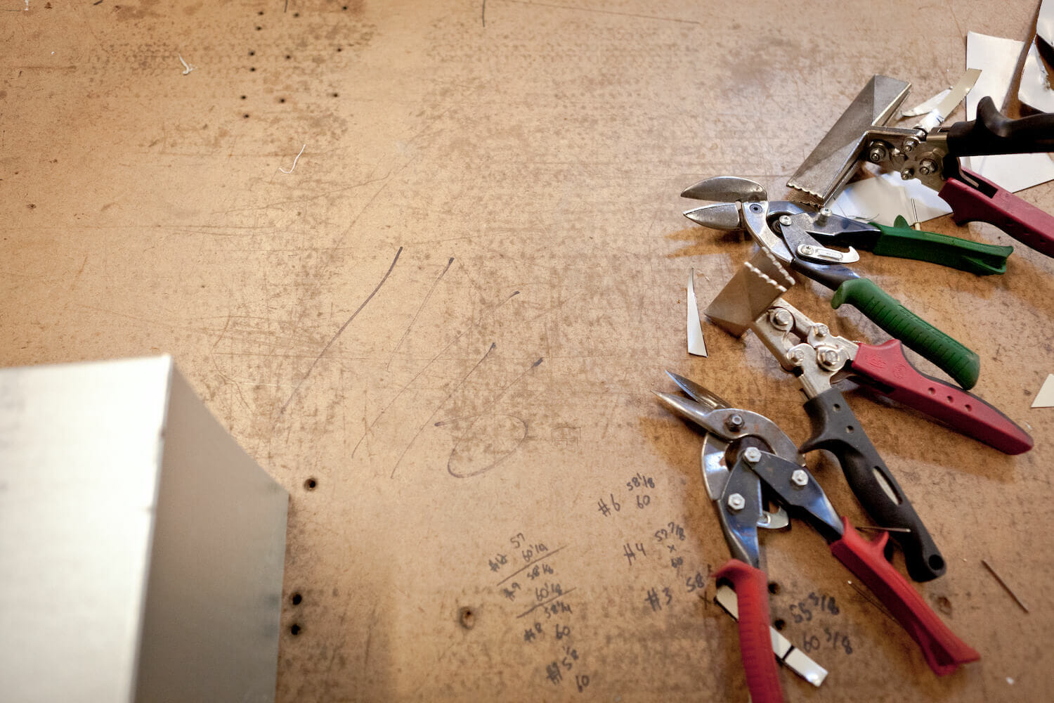 pliers and and wrenches on a brown work table with handwriting