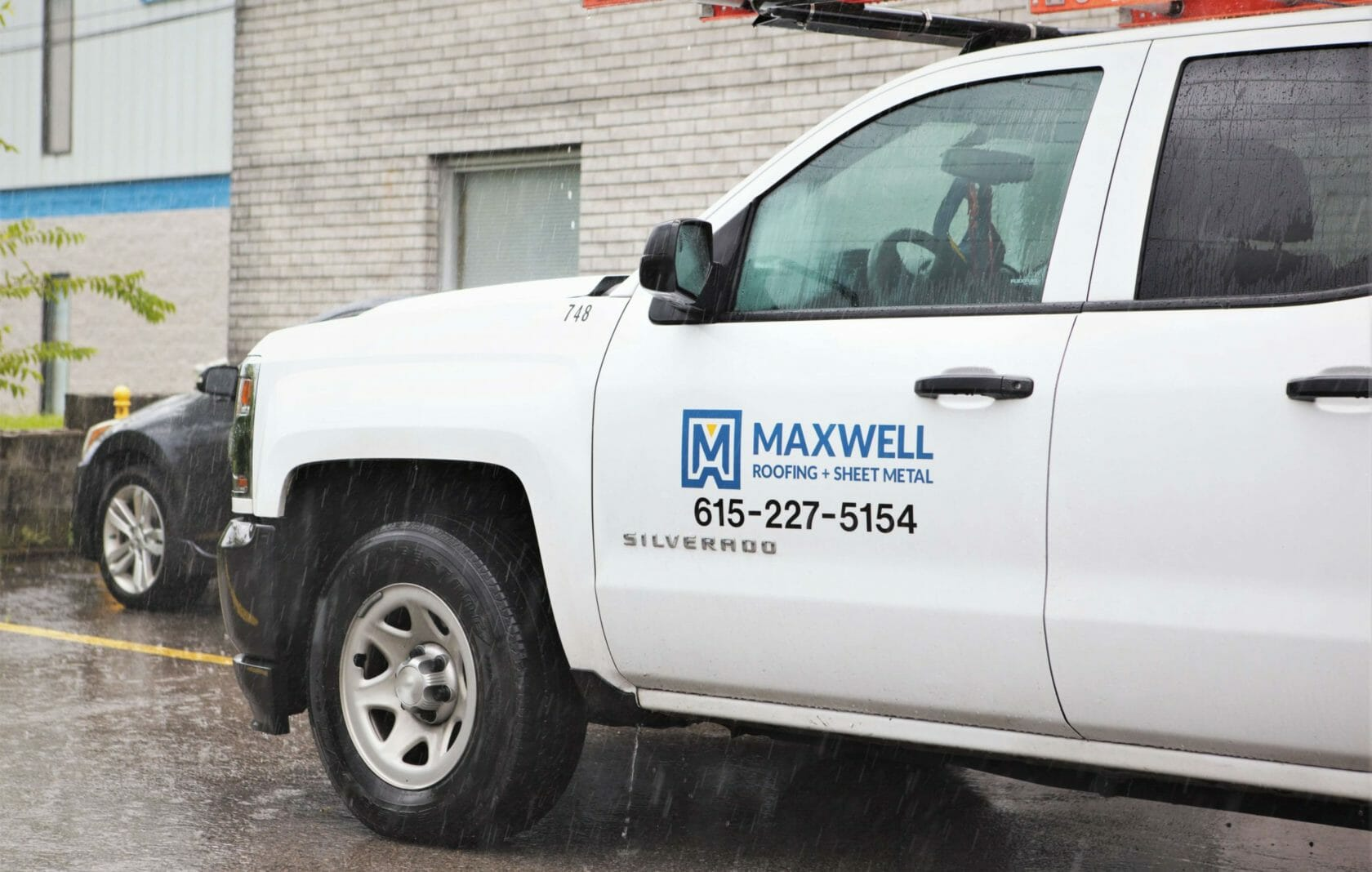 maxwell roofing logo on white service truck
