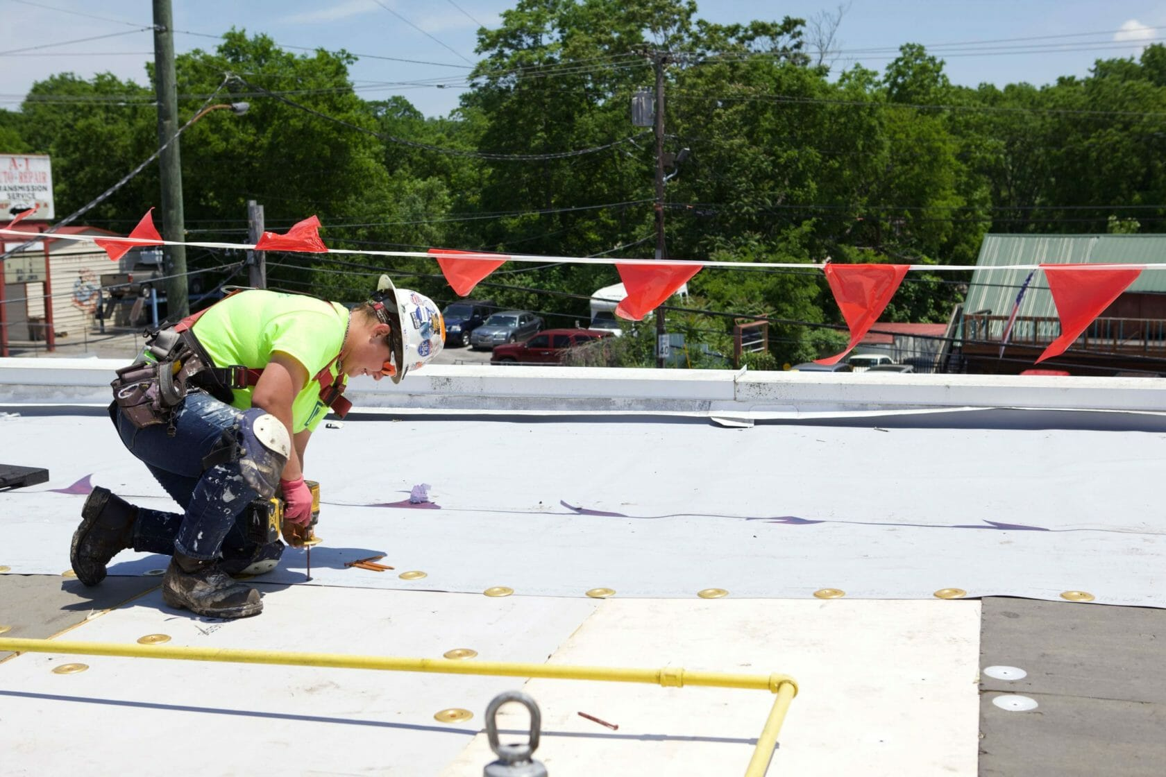 Maxwell roofer using screw driver during roof repair