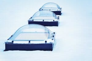 Skylight glass domes on roof of building in snow Helsinki