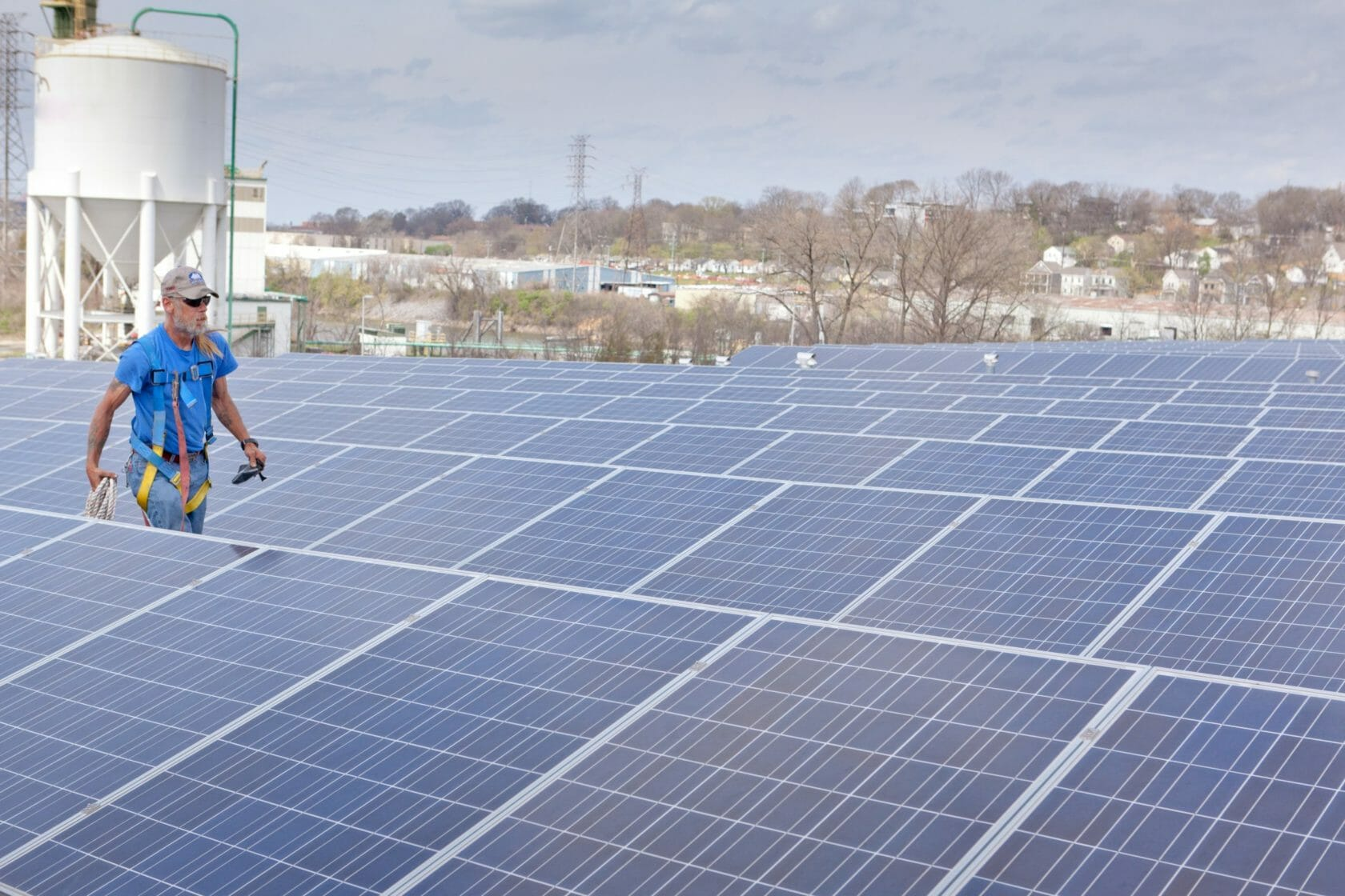 Worker walking through solar panels on a roof