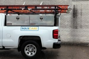 side profile of a white Maxwell Roofing maintenance truck