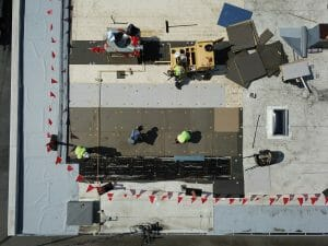 aerial shot of Maxwell roofings working on corner of flat commercial roof