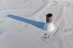 commercial roof with a drain sticking out towards the sky leaving it vulnerable to roof penetration