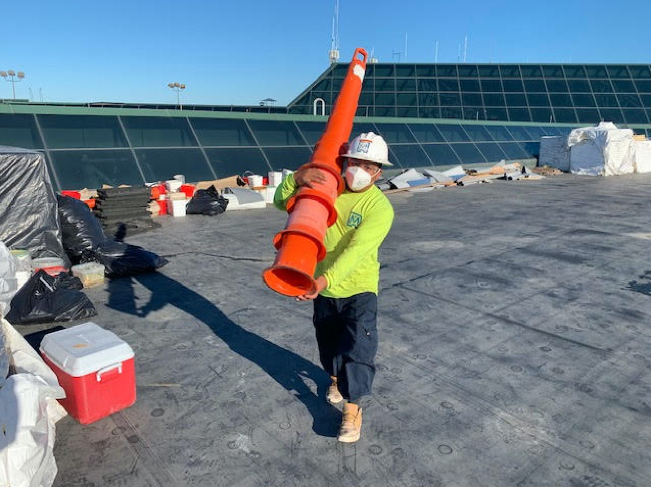 maxwell roofing specialist on commercial roof carrying a large stack of orange caution cones
